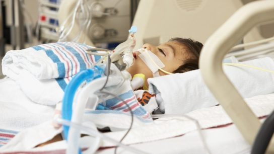 Young boy in ICU hospital bed