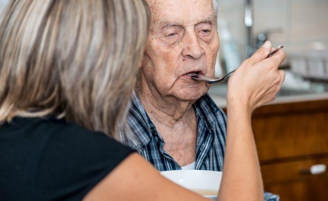 caregiver feeding older man