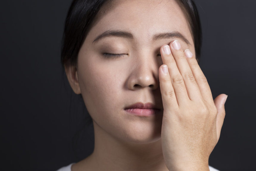 Woman holds hand up to pain behind eye