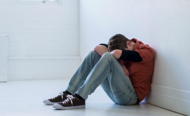 teen boy sitting against wall depressed