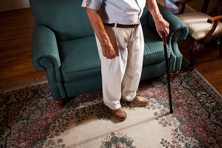 Elderly man standing with a cane.