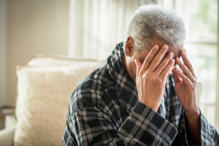 older man holding head in his hands