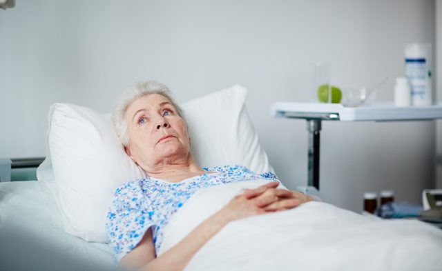 elderly woman laying in bed at a clinic