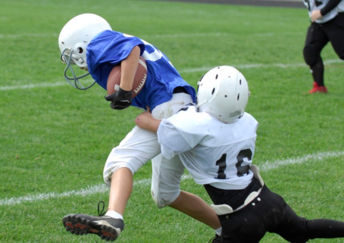 Teens playing football, a contact sport.