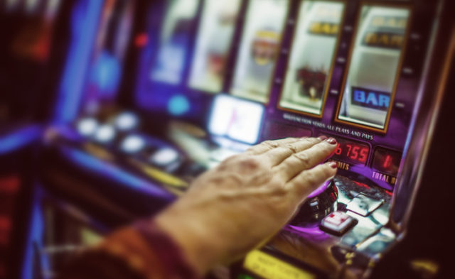 older adult's hand on slot machine