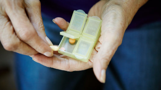 Woman with a pill box and medication