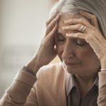 older woman holding her head
