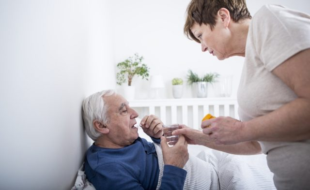wife giving husband a pill