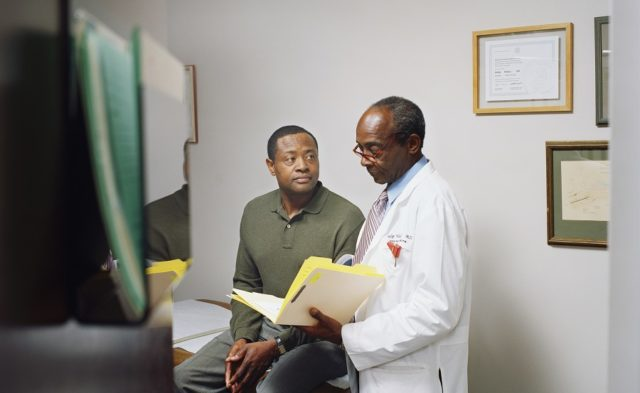 male doctor standing next to male patient