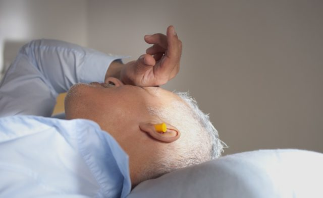 man sleeping with an earplug in