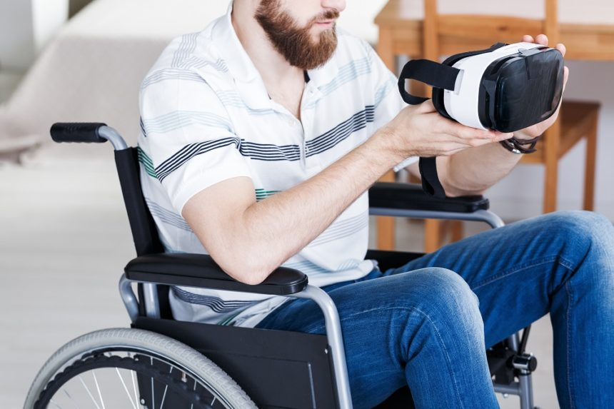 Man in a wheelchair holding virtual reality goggles