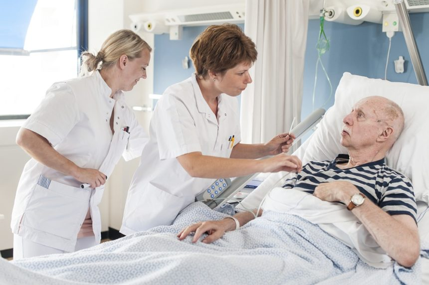 older man laying in hospital bed with two nurses taking care of him
