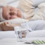 older woman sleeping with sleeping wills on side table