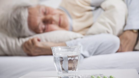 older woman sleeping with sleeping wills on side table