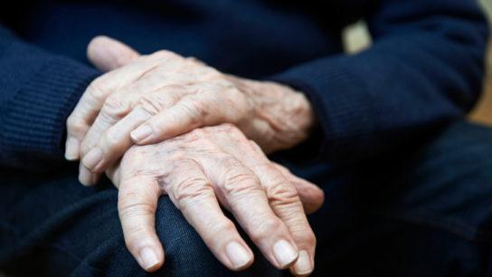 elderly hands resting on knee