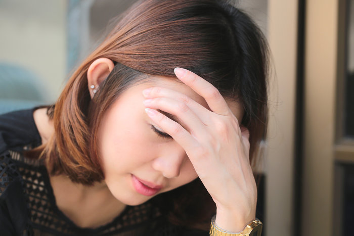 woman holding her head in dizziness