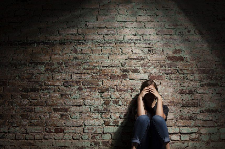 sad woman against brick wall