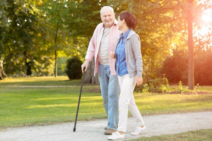 Older man and caregiver going on a walk outside