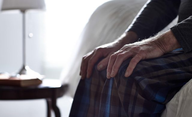 older man sitting on bed with hands on knees