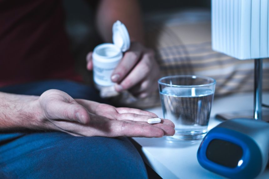 Individual taking pill to aid with insomnia