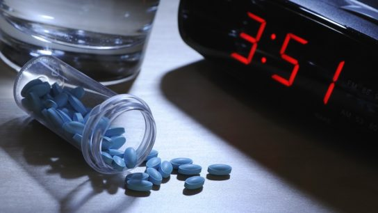 blue sleeping pills next to a clock
