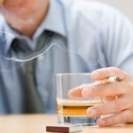man smoking and drinking whisky
