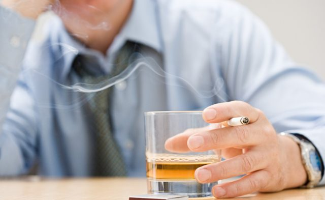 man smoking and drinking whisky
