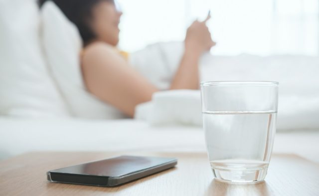 woman in bed with water and phone on side table