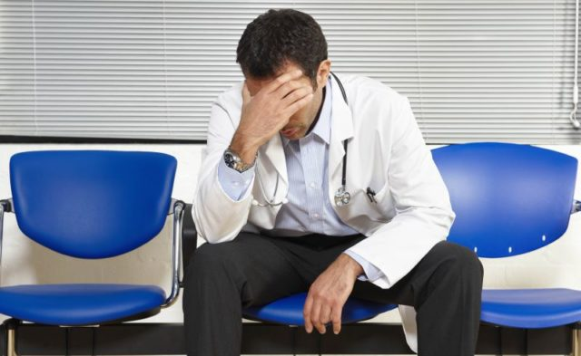 A tired doctor with his head in his hands