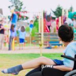 Disabled little boy watching kids play