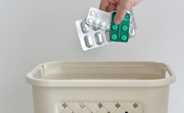 hand throwing away unused pills