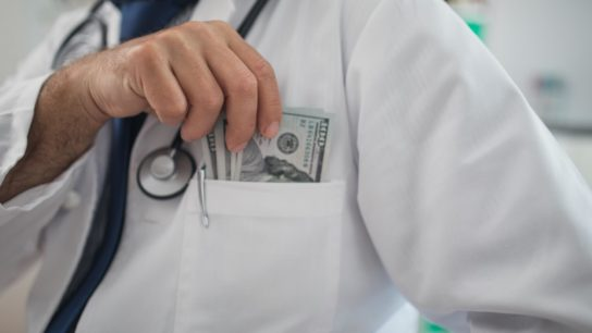 doctor putting money in his pocket
