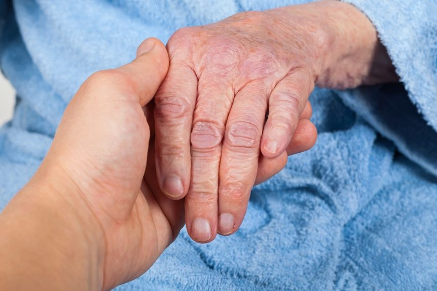 person holding senior woman's hand