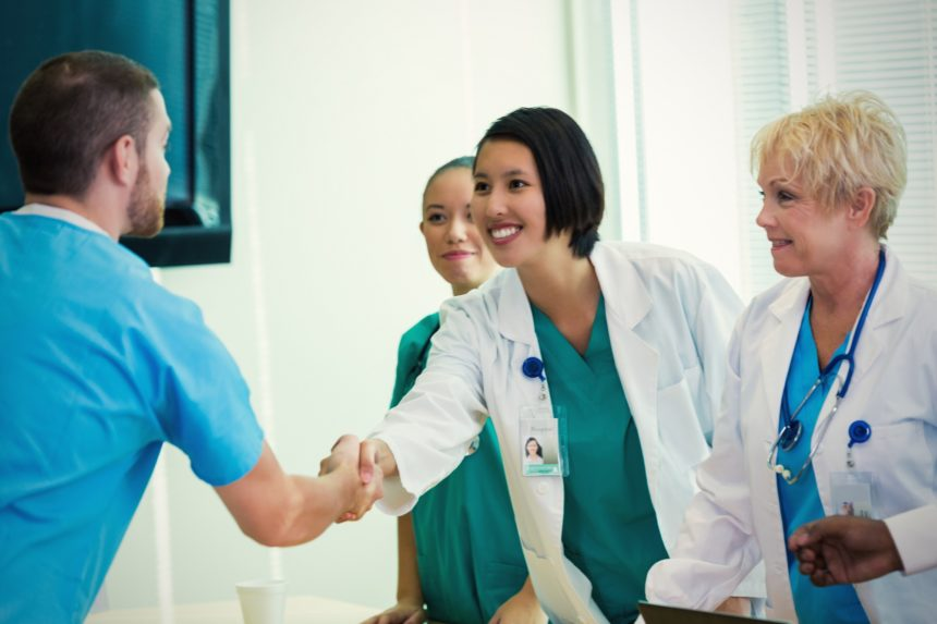 nurse and doctor shaking hands