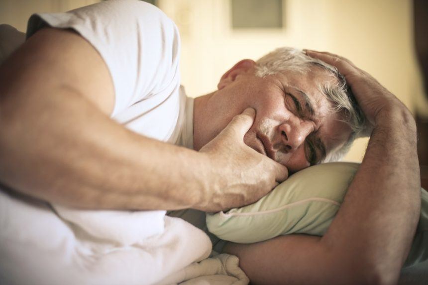 man in bed not able to sleep