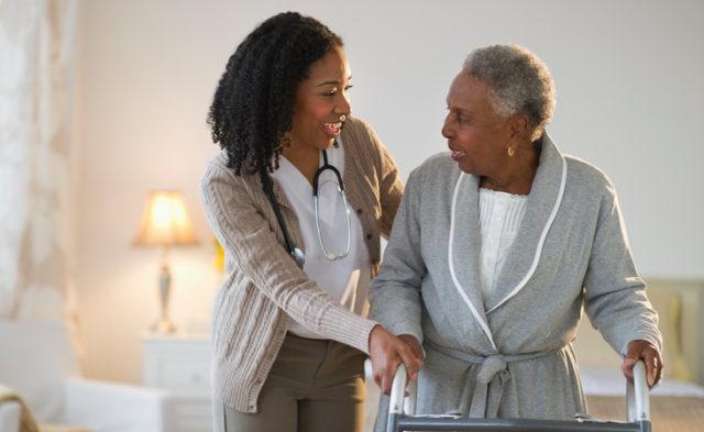 nurse helping older woman with walker