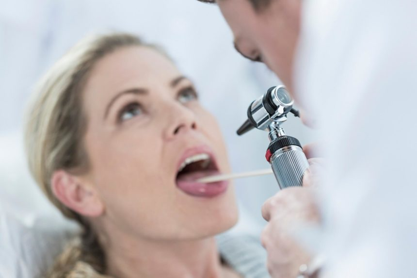 Woman having her throat examined