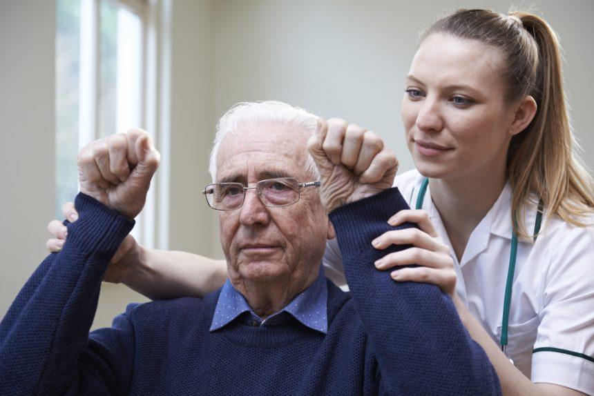 A nurse assesses a stroke victim by raising their arms