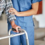 Nurse assisting elderly man with walker