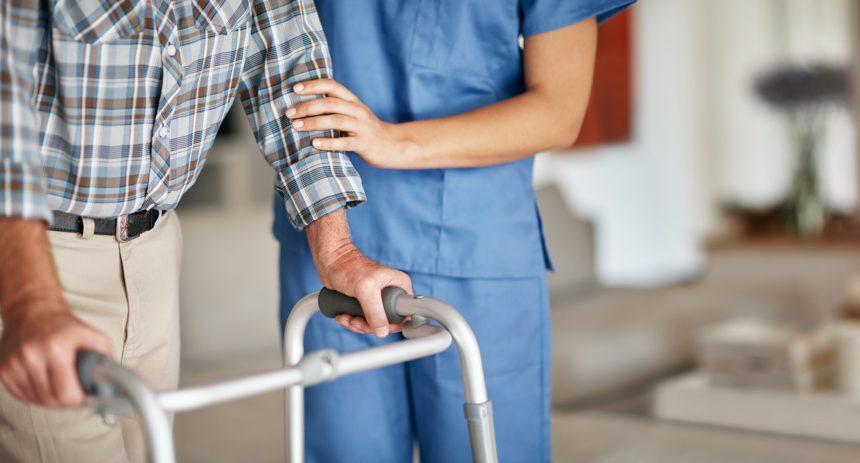 Nurse assisting elderly man with walker
