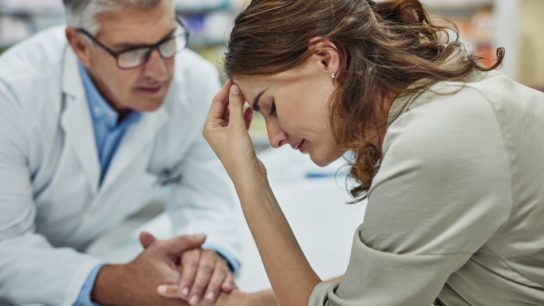 doctor holding hand woman patient headache