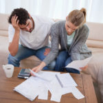 man with headache sitting next to woman looking at finances