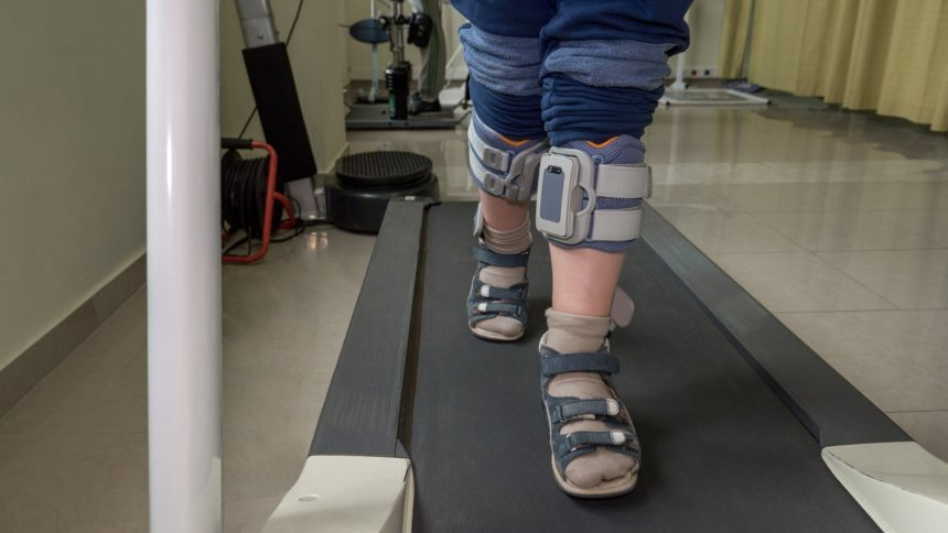 Boy with foot drop system exercising on the treadmill.