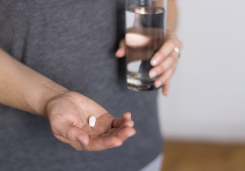 Woman holding white pill and glass of water