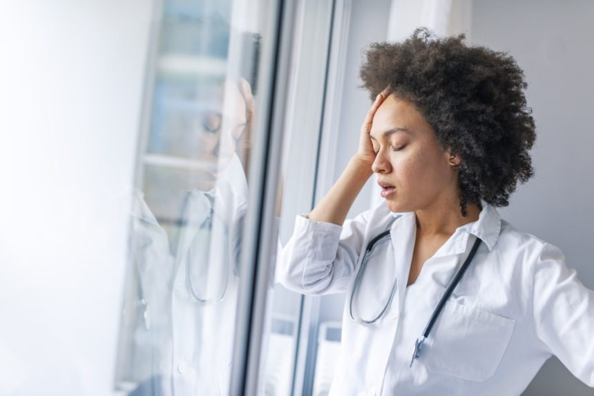 A female physician looks stressed.