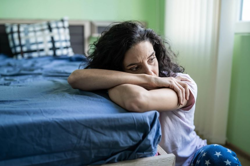 Sad woman sitting on the floor near her bed