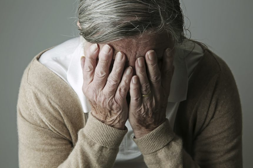 elderly woman covering face, distressed