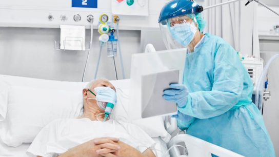 Doctor Showing Digital Tablet To Patient in ICU