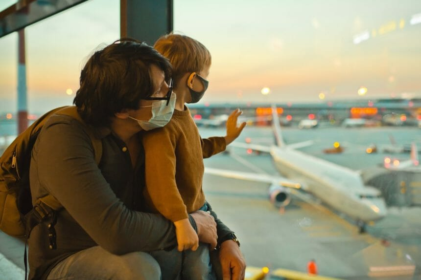 Family in protective face masks in airport during COVID-19 pandemic