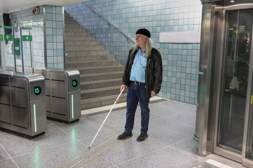 Man with white cane standing at metro station